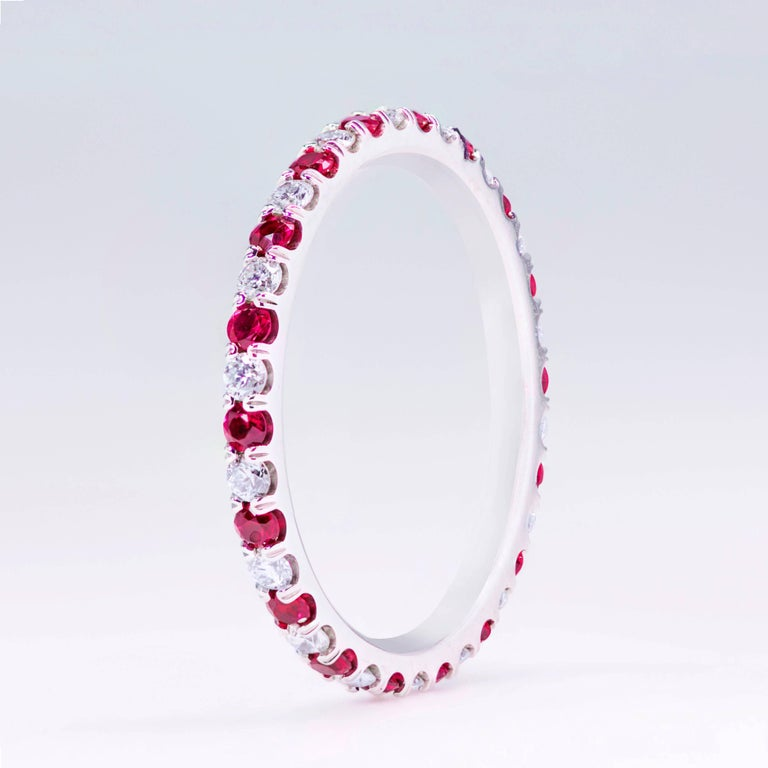 This wedding band features 18 natural rubies weighing 0.44 carats total that alternate with 18 round brilliant diamonds weighing 0.34 carats total. The rubies have a dark purplish red color. Made with 18k white gold. Size 6.5 US.