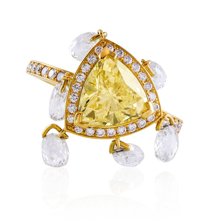 This ring features one triangular diamond graded by GIA. The diamond has a Fancy Yellow color and I1 clarity. It is beautifully surrounded by a single row of round brilliant cut diamonds weighing 0.72 carats total. The center composition accented by