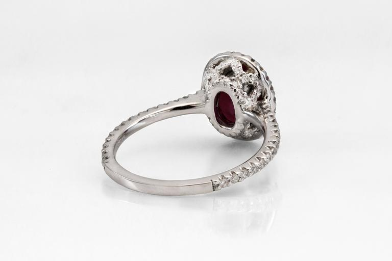 This ring features one natural oval ruby weighing 2.14 carat. The ruby is of very fine quality, it displays a very rich deep red color and eye-clean (has very minor inclusions visible only with the loupe). The ruby accented by the row of round