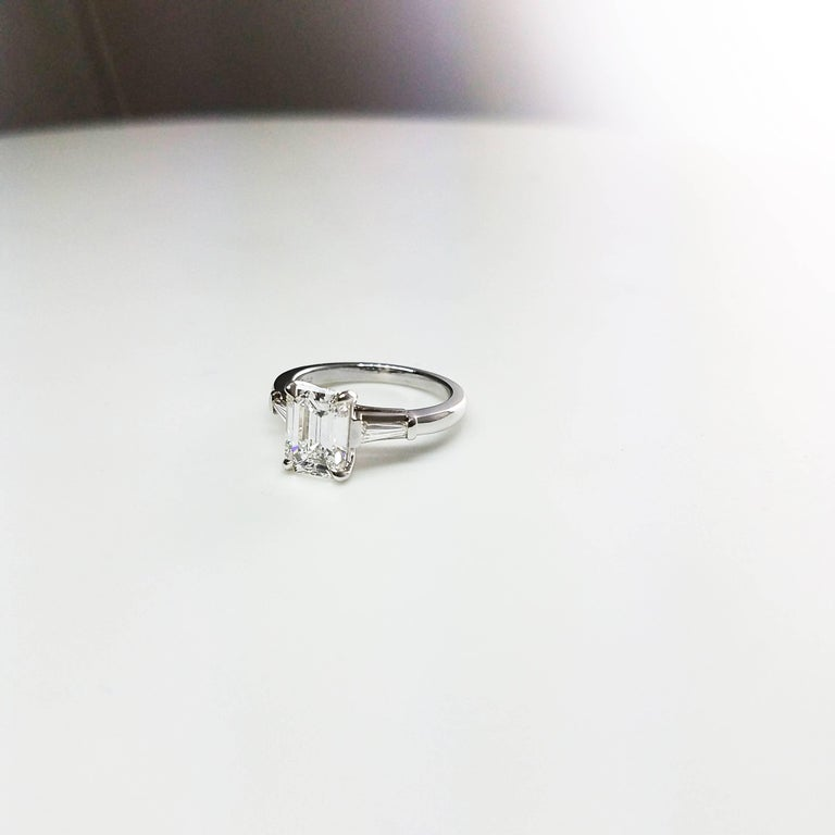 This classy engagement ring features a 1.77 carat emerald cut diamond that GIA certified as H color and VVS2 clarity. The center stone is accented by a tapered baguette diamond on each side. Total weight of the baguette diamonds 0.25 carats. Set in