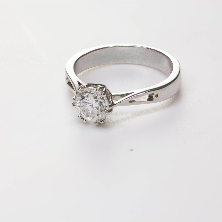 This ring features a round brilliant diamond weighing 1.12 carats that GIA certified as G color SI1 clarity. Set in an intertwining 12 prong setting. Made in 18k white gold. Size 6.5 US (sizable upon request).   Style available in different price