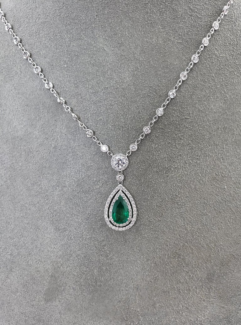 The pendant showcases a 1.28 carat pear shaped green emerald center stone surrounded by two rows of dazzling diamonds. Suspended on a round diamond that is attached to a diamonds by the yard chain. Total weight of the diamonds 2.51 carats. Crafted