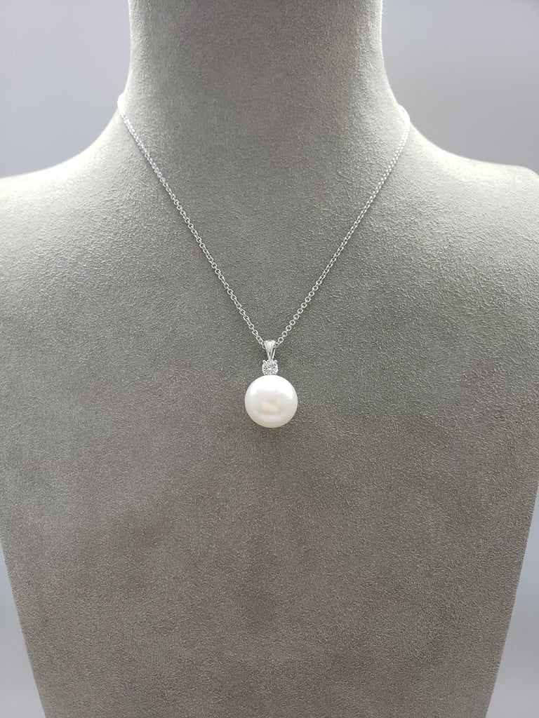 A pearl necklace showcasing a 14 millimeter South Sea pearl accented by a single brilliant round diamond weighing 0.26 carats total. Set in 18 karat white gold. Attached to a 18 inch white gold chain.