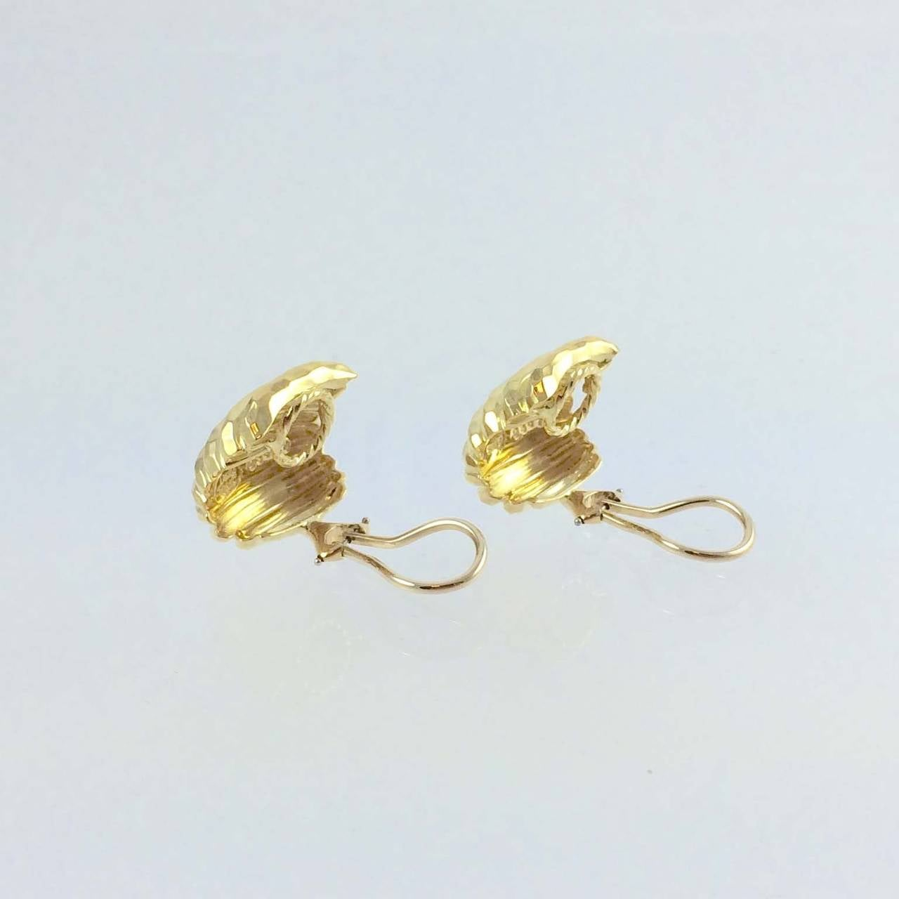 18K yellow gold faceted Henry Dunay ear clips, with omega backs.  Measuring 19.8mm long by 18.2mm wide