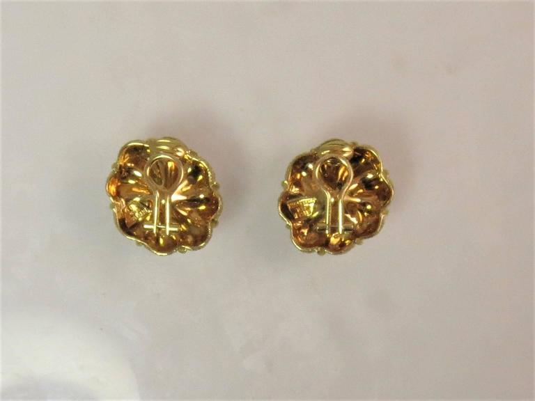 Signed Tiffany 18K yellow gold diamond flower ear clips, set with two full cut round diamonds weighing .75cts, G color, VS clarity, weighing 27.8 grams.