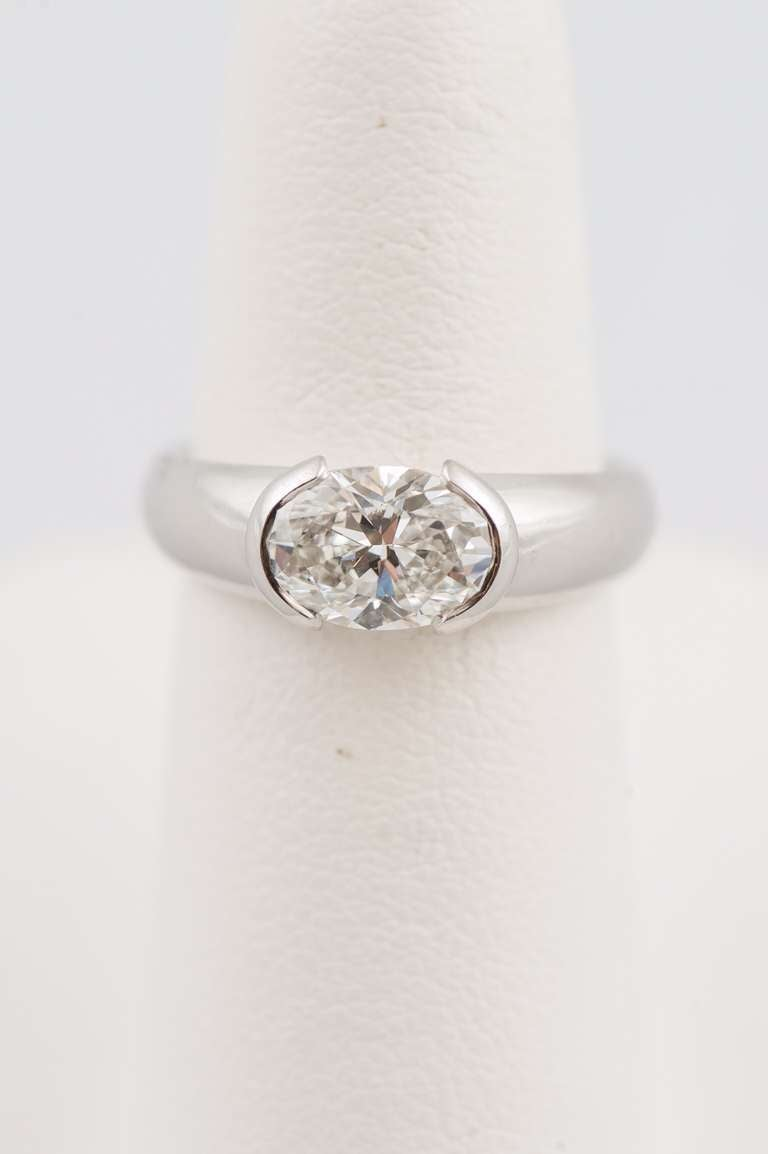 """Oval diamond, weighing 1.50 carat, F color, VVSI clarity, GIA certified, horizontally set in a partial bezel """"Hudson"""" style high polish platinum mounting by Michael Bondanza.  Finger size 6. May be sized."""