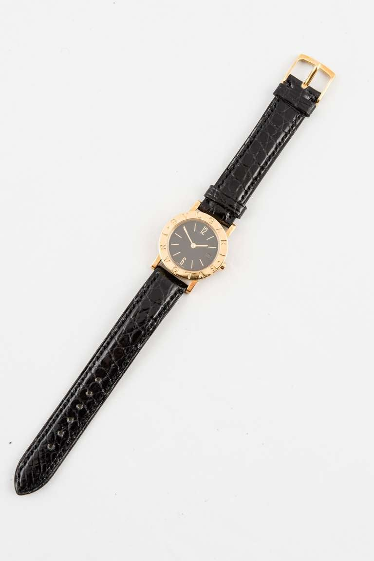 Brand new, never worn Bulgari lady's 18k yellow gold wristwatch, quartz movement, black dial, date, Arabic numerals at 12 and 6, gold baton markers, with black alligator strap and 18k yellow gold ardian buckle, style number BB26GL. Last retail