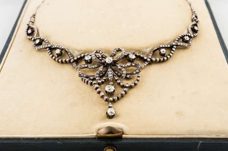 Edwardian Silver over Gold, Flexible  Diamond Necklace in its original fitted box from A. Leroux, 1 Rue Dumes, Le Mans, with 11 European cut round diamonds prong set,  H-I color, VS-SI clarity, weighing about 2.75 carats total, and 300 rose cut