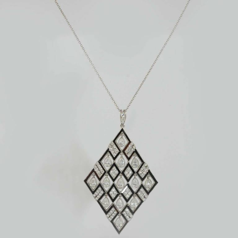 Platinum pendant bezel set with (milgrain edge) 13 dangling pear shape diamonds weighing 1.72 carats total and 83 single cut round diamonds weighing .98 carats additional, with onyx sections detailing the kite shapes, suspended from 16 inch platinum