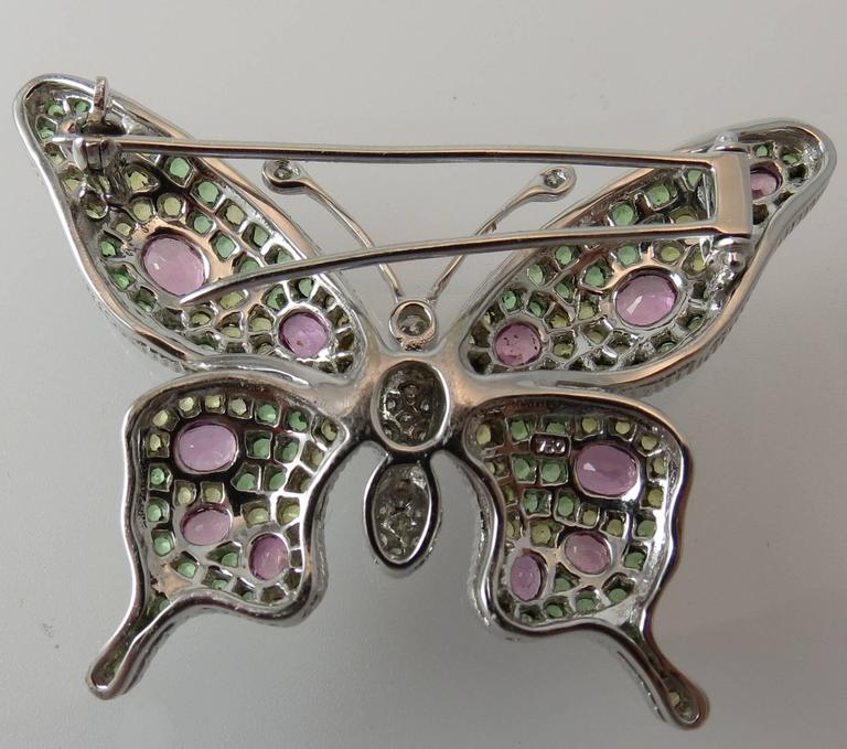 18K white gold Butterfly pin set with 17 round diamonds, pave set, weighing  .29cts,12 oval pink sapphires, prong set, weighing 2.71cts, 75 yellow sapphires, prong set, weighing 1.87cts and 70 tsavorites, prong set, weighing 2.23cts.