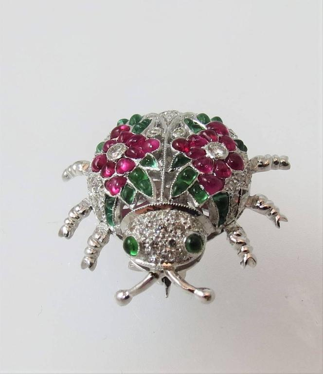 Fabulous 18K white gold beetle pin, set with 20 cabochon rubys, 28 cabochon emeralds, and 47 round diamonds about 1.20 cts, with adorable articulating legs.