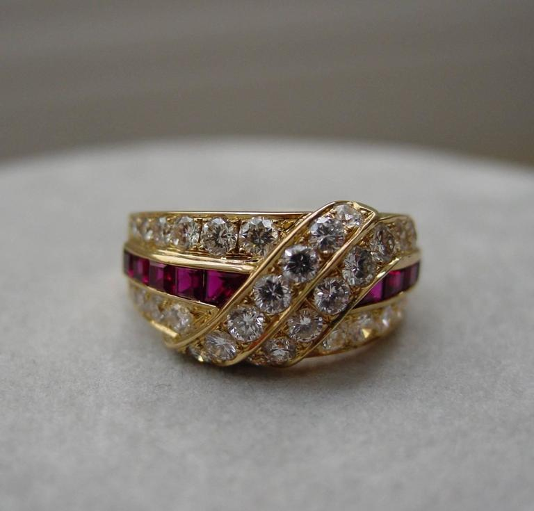 A diamond and ruby ring by Van Cleef & Arpels mounted in 18 karat yellow gold. This classic ring is set with thirty four round brilliant diamonds weighing approximately 1.40 carats and ten rubies weighing approximately .40 carats. Signed VCA