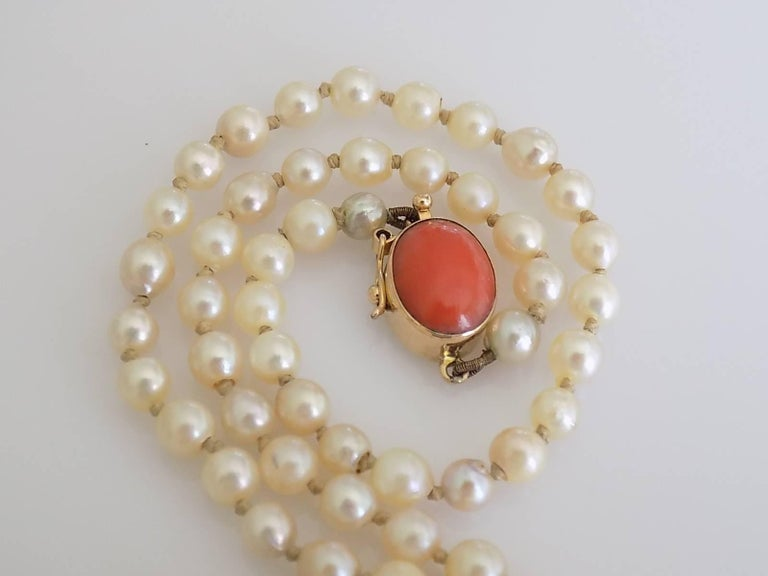 A Lovely Art Deco c.1920s hand knotted Opera length Cultured pearl necklace on 18 Carat Gold and Coral push in clasp. Length including clasp 30 inch;. Pearls approx. 4mm. Weight 16.5gr. Marked 750 for 18 Carat Gold.