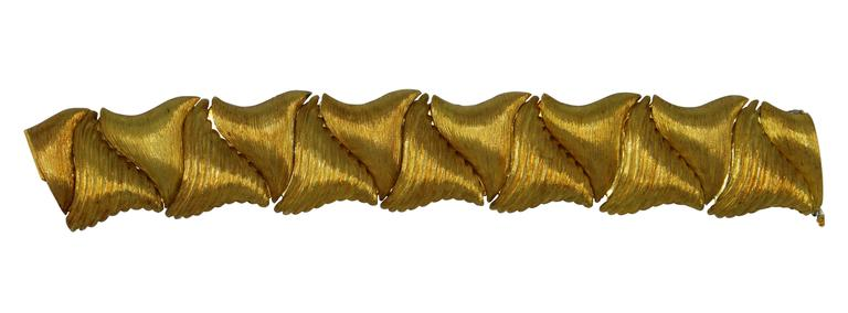 Highly sculptural textured gold link bracelet by Henry Dunay, designed as modified triangular yellow gold sections with alternating textures, mounted in 18 karat yellow gold, gross weight 101.6 dwts., length 7 1/8 inches, width 1 1/8 inches, signed