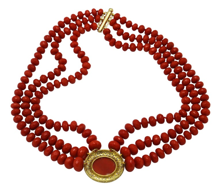 A fantastic 1960s multi-strand coral bead necklace composed of three strands of graduated coral beads, completed at the center with a circular plaque set in the center with a round cabochon coral segment, framed by round diamonds weighing