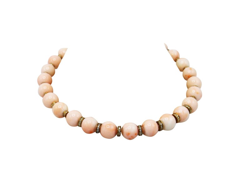 18 karat yellow gold, coral bead and diamond necklace, of graduated design composed of natural pink coral beads with beautiful variations of color measuring 13.5 to 11.5 mm., spaced by gold rondelles set with round diamonds weighing approximately