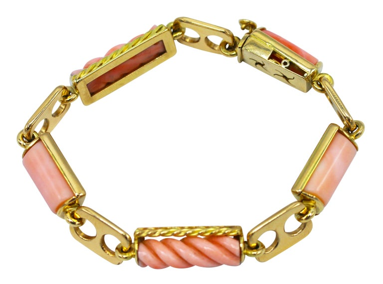 Handmade 18 karat yellow gold and pink coral bracelet, Italian, circa 1970, designed as alternating openwork rectangular gold links spaced by sections of carved and ribbed pink coral in gold frames, gross weight 43.0 grams, length 7 3/4 inches,