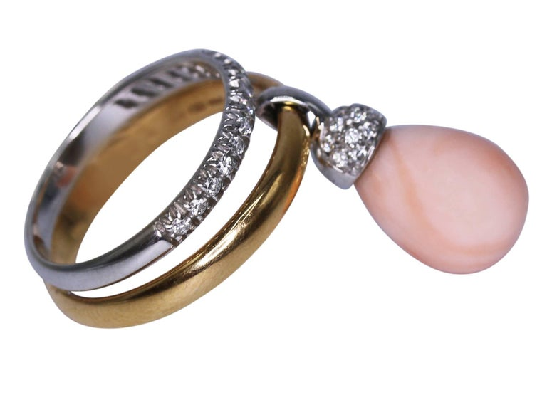 18 karat white and yellow gold, angel skin coral and diamond ring by Chantecler, Italy, designed as a polished yellow gold band and diamond-set white gold band accented by a angel skin coral pendant capped by diamonds, total diamond weight 0.50