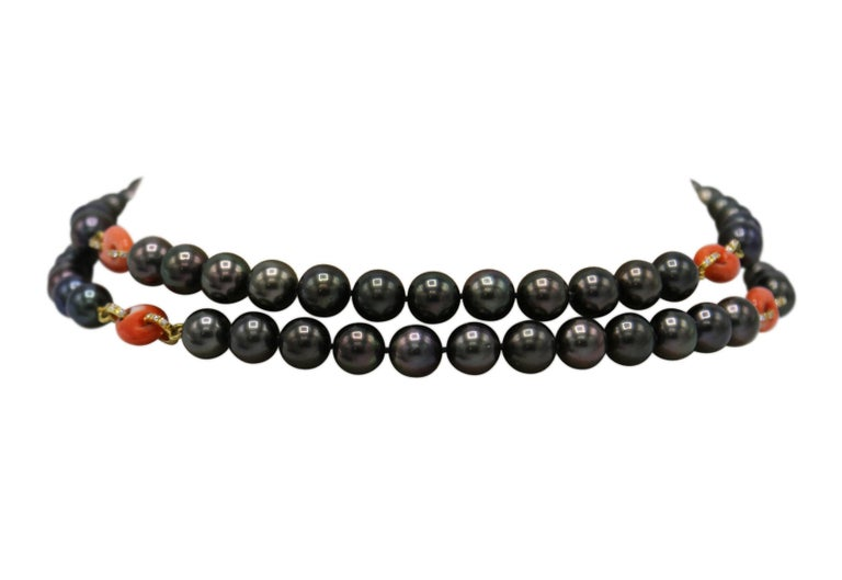 18 karat yellow gold, Tahitian black pearl, natural coral and diamond necklace, the single-strand composed of numerous Tahitian black pearls measuring 10.0 to 14.0 mm., spaced by carved coral links accented by round diamonds weighing approximately