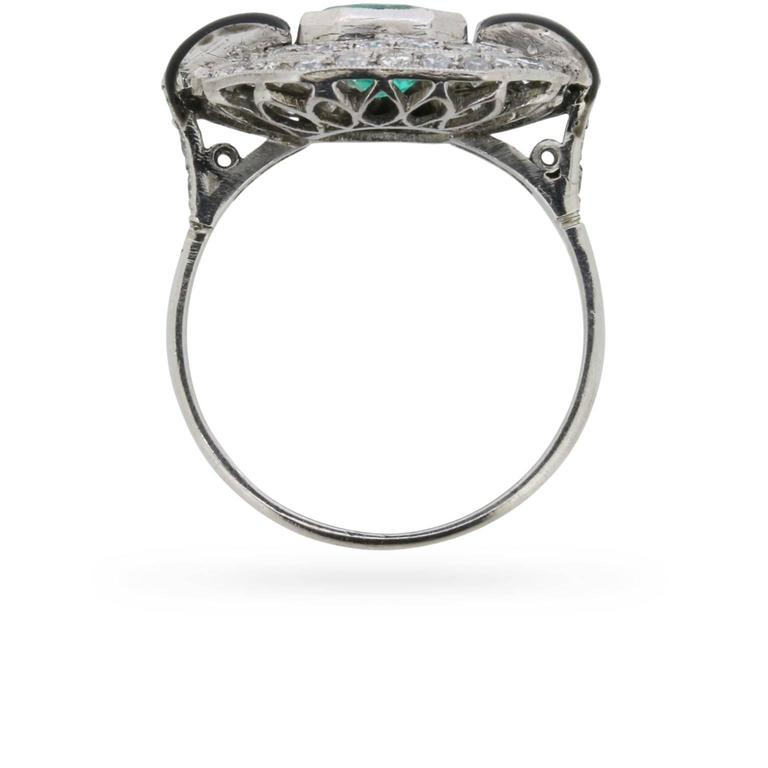 This vintage c.1950s ring, crafted in platinum and diamonds with black enamel accents, is designed around a 1.50 carat emerald.  A double octagonal halo of grain-set round brilliant cut diamonds that totals to 0.60 carats, embellishes this colourful