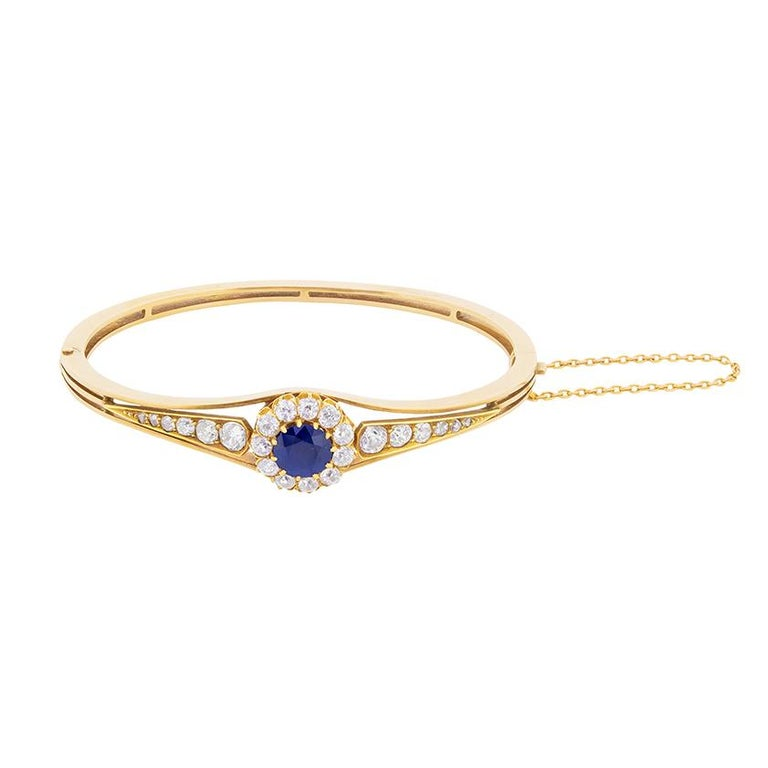An old cut sapphire surrounded by a halo of old cut diamonds is the centrepiece of this late Victorian era bangle bracelet. The Sapphire weighs 1.80 carat and is a wonderful deep blue. The diamonds, which dazzle with their colour, estimated f and