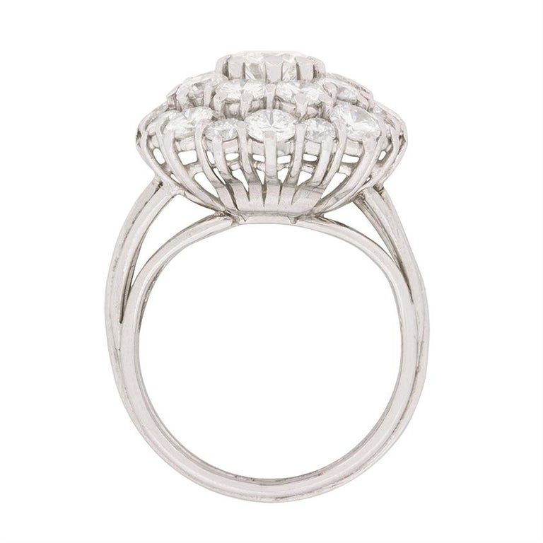 A vintage cluster ring, which boasts a centre stone of 0.50 carat and the surrounding round brilliants totalling 2.80 carat. The colour is graded F and the clarity VS2 which becomes apparent through it's shine and sparkle. The diamonds are claw set,