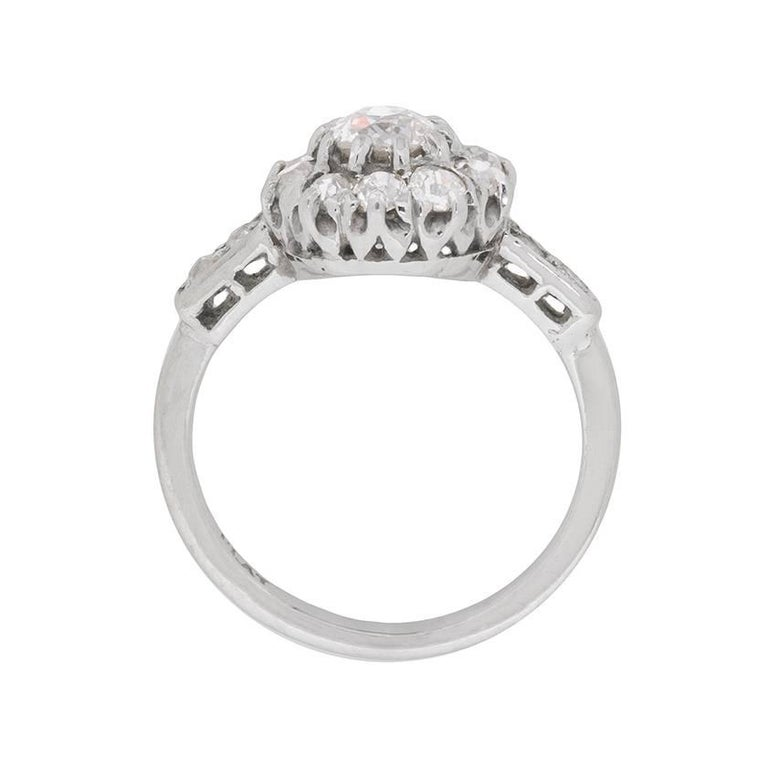 This art deco cluster ring, made entirely of platinum, boasts a centre stone of 0.65 carats. This is then haloed by another 10 diamonds, just as dazzling, within the claw setting. To finish off the diamond collection, there are 2 little old cuts