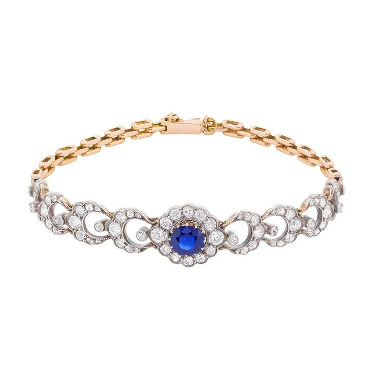 This stunning Edwardian bracelet features a claw set central sapphire which is an impressive blue. The natural gemstone weighs 1.35 carat and has no evidence of heat treatment. It is beautifully surrounded by a halo of old cut diamonds totalling to