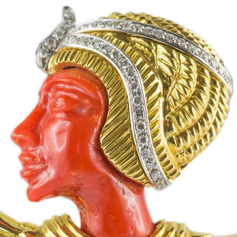 This egyptian revival style 18KT yellow gold brooch can also be worn as a pendant. Embellished by brilliant cut diamonds, the profile and the bead are in 9 ct. coral.