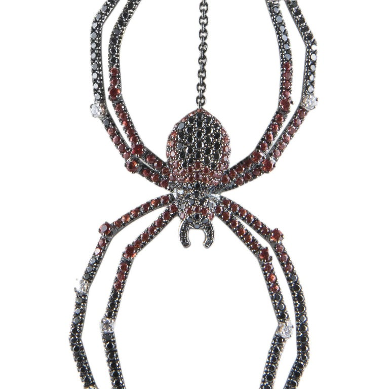 Unique 18 Karat white gold long necklace from our Lullaby Collection. The spider pendant is form by  1,66 ct. of brilliant cut black diamonds, 0,43 ct. of brilliant cut white diamonds and 1,21 ct. of orange sapphires. The chain is 95 cm long and