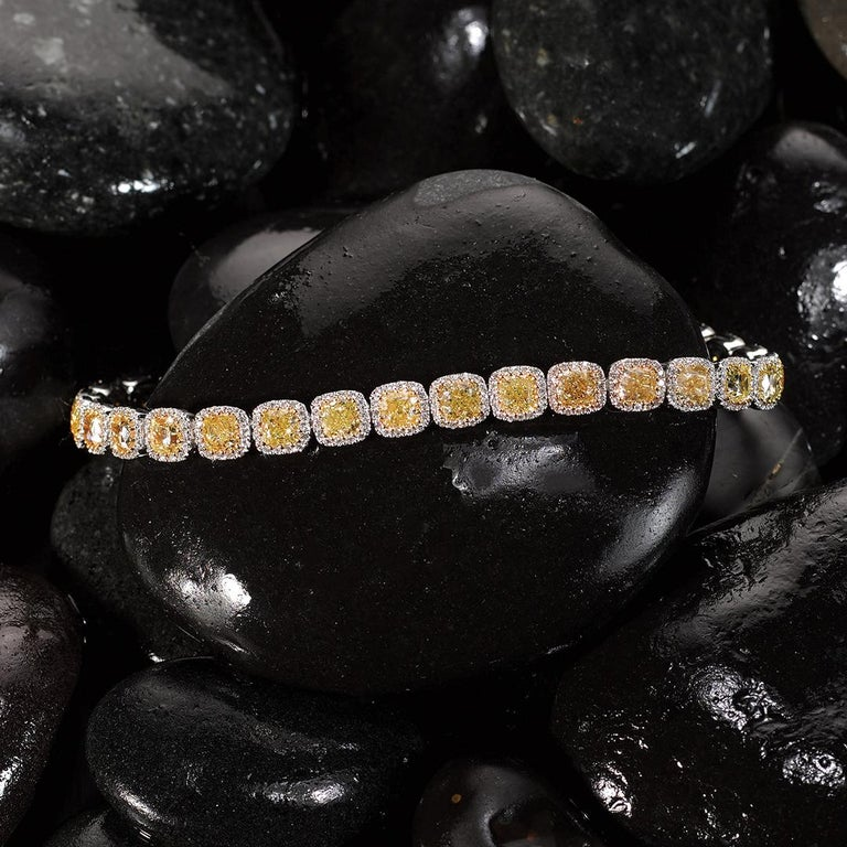 Our striking Matthew Ely Yellow Diamond Bracelet features a selection of 28 timeless Cushion Cut Fancy Yellow Diamonds totalling 12.18cts, surrounded by 412 White Diamonds totalling 1.07cts (color F / G clarity VS) encased in two tones 18ct White