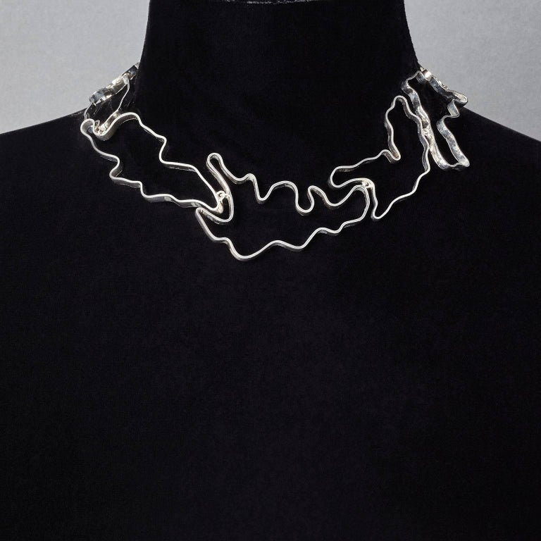 Made by hand in Nathalie Jean's Milan atelier, the Informe contemporary small choker necklace is composed of 11 elements articulated of varying dimensions in polished sterling silver ribbon. It's little connecting rings allow the piece to drape