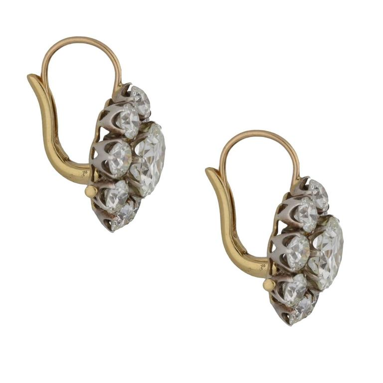A truly phenomenal pair of detachable diamond cluster drop earrings set in platinum and 18ct yellow gold. Each earring is formed from a nine-claw set central old cut diamond which is permanently attached to the central diamond from the cluster, the