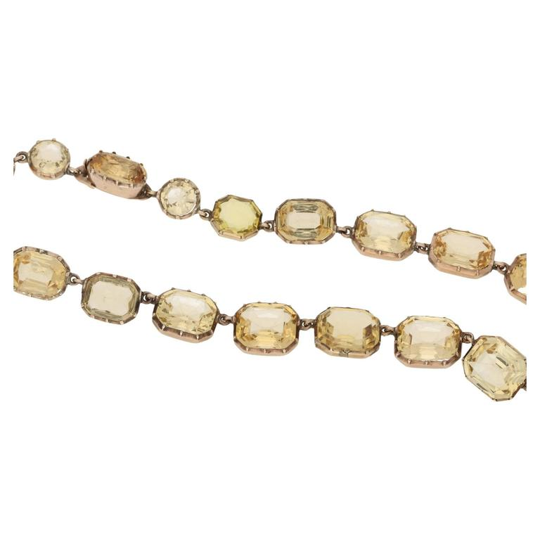 An important Victorian Imperial topaz riviere necklace set in  yellow gold. Comprising of long oval topaz hiding a tongue in groove clasp, shouldered by a pair of round faceted topaz's and completed with twenty five graduated rectangular scissor cut
