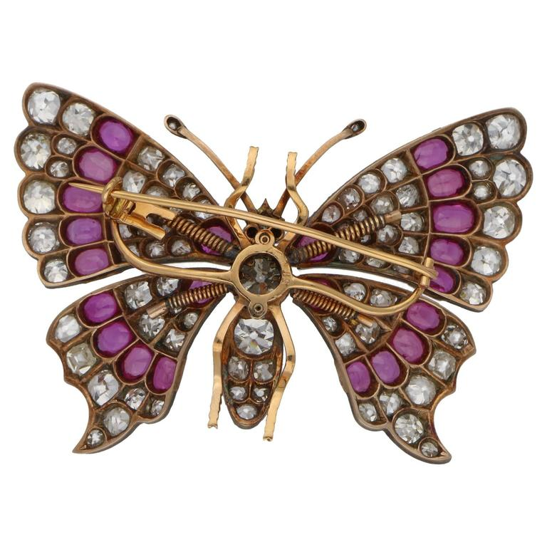 A stunning butterfly brooch set in 18ct rose gold and silver, featuring sprung set fluttering wings grain set with diamonds and rubies. The body of the butterfly is grain set with diamonds, featuring one large 1.44ct Old European cut diamond in the