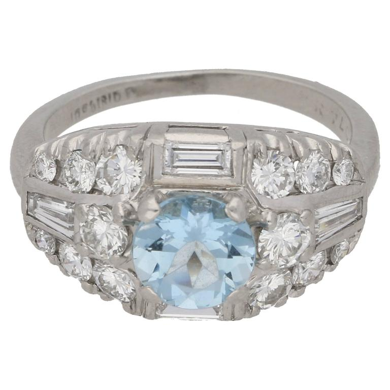 An Art Deco aquamarine and diamond bombe cocktail ring in platinum. The ring features a round-shape aquamarine four-claw-set to the centre, amidst a bombe-shape collet rubover- and claw-set throughout with baguette-cut, tapered baguette-cut,