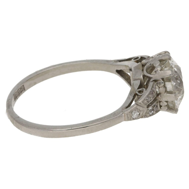 A very unique platinum single stone engagement ring featuring a K Si2 2.47ct Old European cut diamond in an eight claw setting with shield shaped shoulders. Each grain is set with five old cut diamonds to a straight 1.50mm width shank. The ring