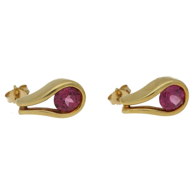 A colourful pair of vintage pink tourmaline stud earrings. Each earring is formed of one round brilliant cut tourmaline set into an 18 carat yellow gold tear drop shape mount, they are hallmarked 750 and 'Diana Vincent'.
