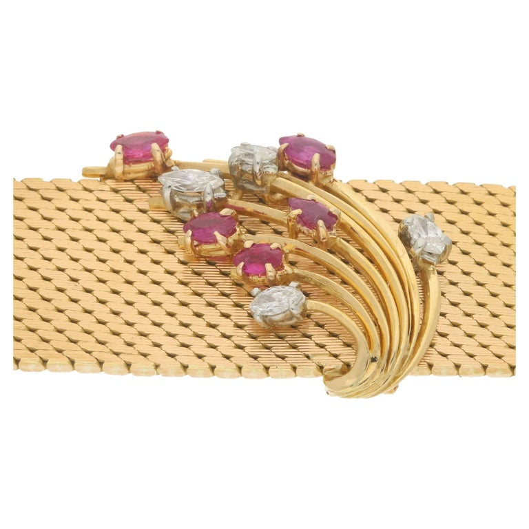 An early 1960's ruby and diamond gold bracelet. The bracelet is formed of a Milanese weave in 18 carat yellow gold with a central motif consisting of a ruby and diamond spray. The bracelet has a double locking safety clasp.  Estimated total diamond