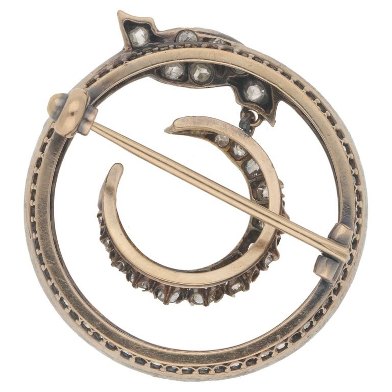 A Victorian Crescent moon diamond brooch, featuring 52 diamonds with an approximate total carat weight of  2.40cts, and estimated as H/I colour and Pique clarity.  The brooch features a circular scroll border grain set with 39 point cut diamonds,