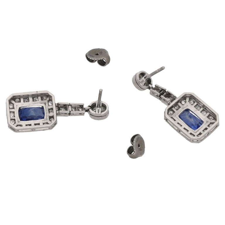 A pair of diamond and sapphire drop earrings set in 18ct white gold featuring an old mine cut diamond estimated as 0.40 carats I/J colour and Vs clarity in a millegrain rubover setting to a post and butterfly fitting from which drops an articulated