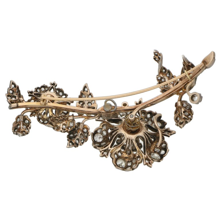 A notable Victorian diamond brooch set in silver on gold, designed as a floral and foliate spray centering on a detachable flower head set