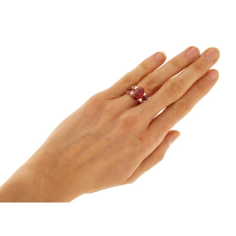 Alex Jona one-of-a-kind design collection, designed and hand crafted in Italy, 18 Karat rose gold ring, set with an oval cabochon tourmaline weighing 5.50 carats. On either side of the center stone a split shank set with brilliant-cut round white