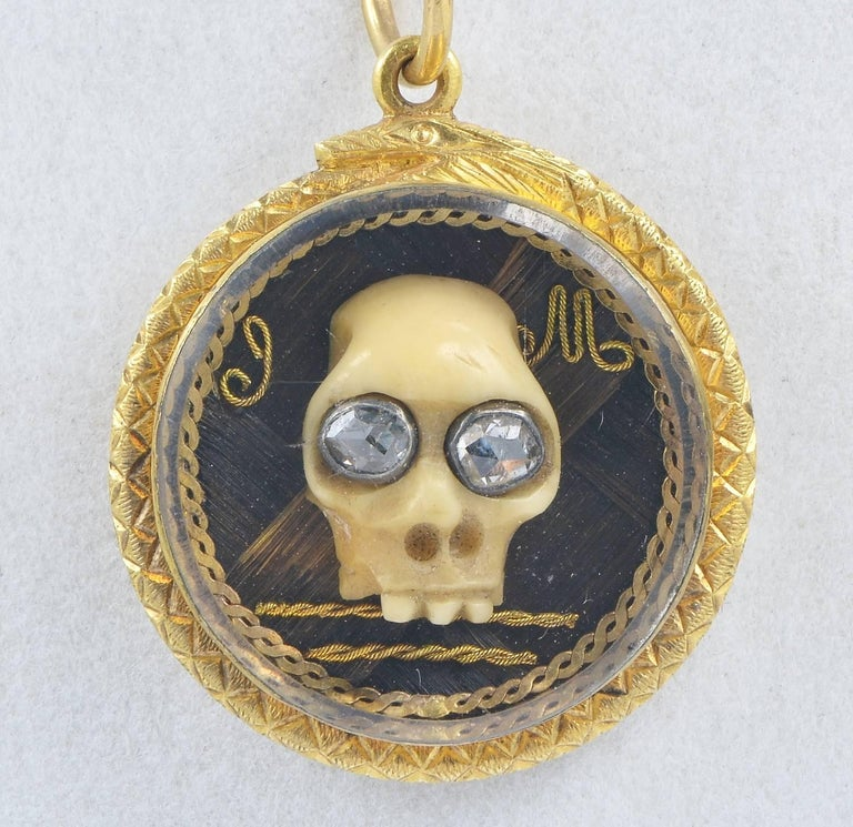 rare 22 KT solid gold pendant of the Georgian period  a Memento Mori Skull with Diamond eyes is kept under a rare Stuart Crystal Close back setting beautiful detailed with a snake biting its tail in sign of eternity artwork hair in the inside with
