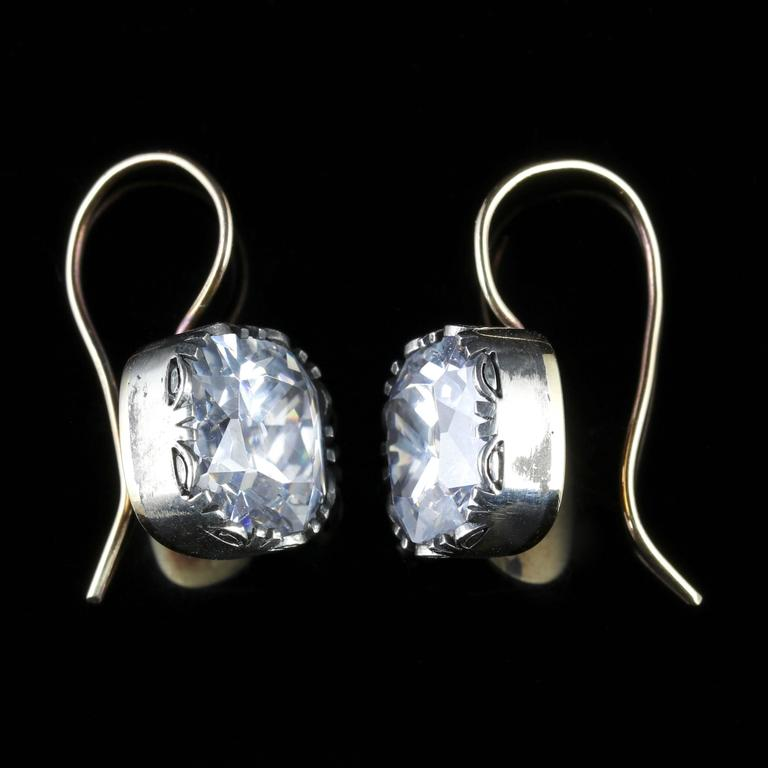 These fabulous white Paste earrings boast a 5ct Paste stone in each earring, if not larger.  They are Collet set in Silver and presented in a lovely square cushion cut gallery.   These have been made from a Georgian collar, a small hole is at the