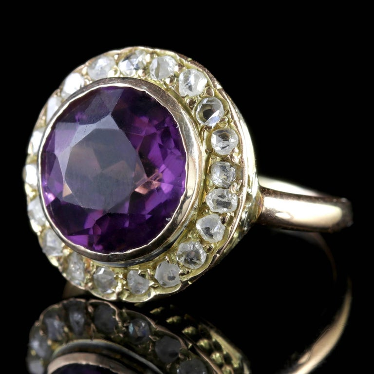 To read more please click continue reading below-  This genuine antique Victorian 18ct Yellow Gold ring boasts a 5ct natural Amethyst in the centre surrounded by a halo of Diamonds.  Amethyst has been highly esteemed throughout the ages for its