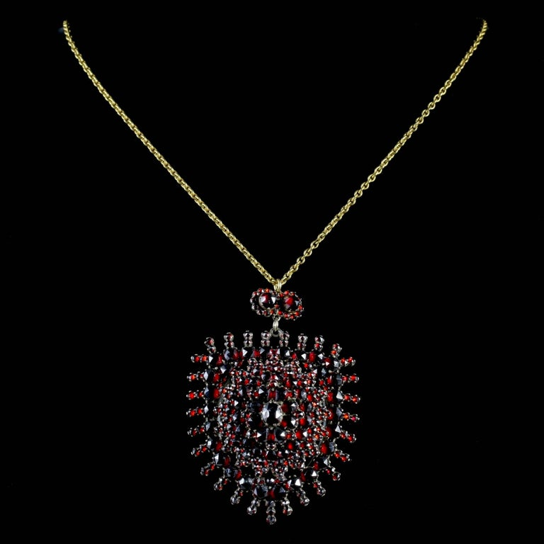 To read more please click continue reading below-  This magnificent antique Bohemian Garnet pendant Locket and chain is genuine Victorian Circa 1890.  The beautiful large pendant is adorned with a stack of deep red Bohemian Garnet's set in a