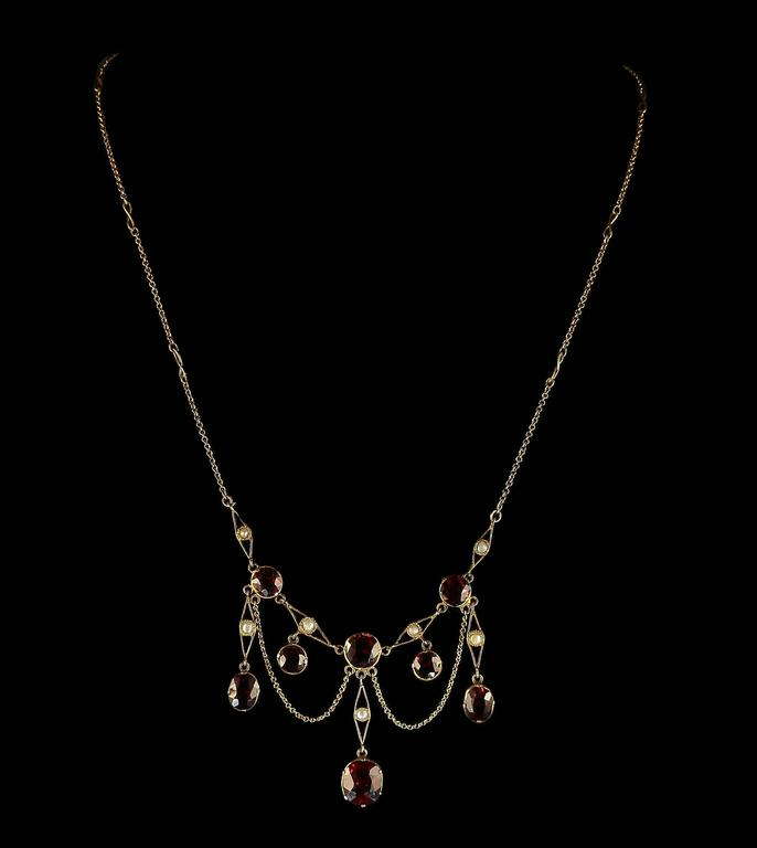 This fabulous 18ct yellow gold necklace is adorned with beautiful rich deep garnets and pearls.  The bottom garnet is 4ct alone, with swags of gold making a fabulous garland of garnets and pearls.  The necklace is fancy with lovely S panels around