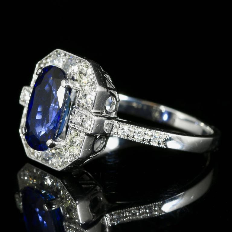 This is a very beautiful 18ct white gold ring which boasts a fabulous rich blue sapphire and encrusted with old cut diamonds.  The ring is set with a 2.50ct sapphire in the centre which is surrounded by magnificent diamonds, even taper down the