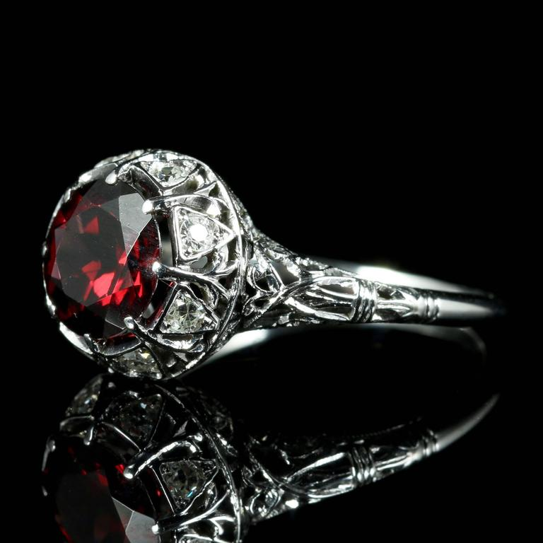This fabulous Antique all platinum ring is Circa 1920.  Set with a deep red Garnet and old cut Diamonds which are set into the gallery of the ring.  The Antique ring has been tested as platinum.  The lovely deep red natural Garnet has a lovely red